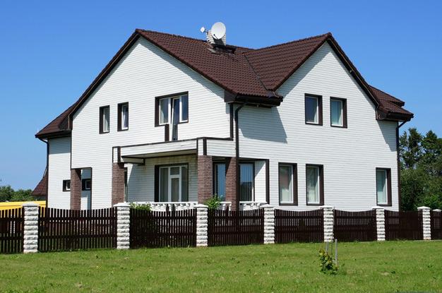 Деревянный забор из штакетника перед фасадом дома